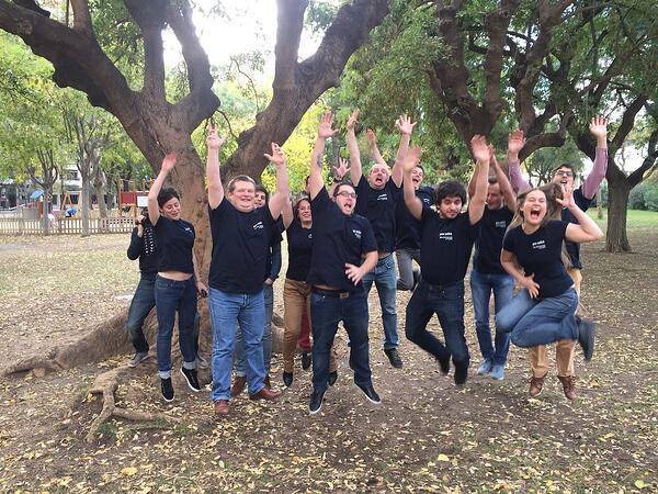 Group of people jumping in the air under a tree