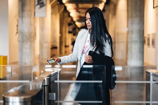 woman using QR code to enter turnstile